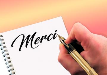 """Organiser un événement - Main qui écrit """"Merci"""""""