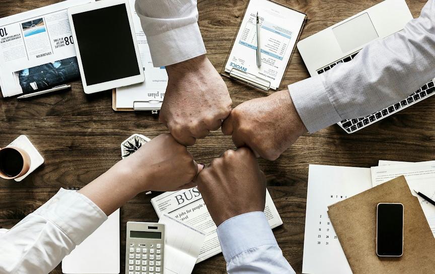 Image associée à Faire un don - 4 mains ensemble au-dessus d'un burau avec calculatrices