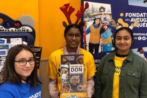 3 bénévoles dont une tenant une boite de dons, sourient à la caméra