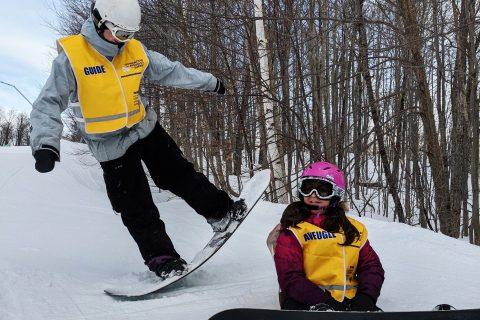 Un accompagnateur soulève un côté de sa planche à neige alors qu'une participante est assise dans la neige