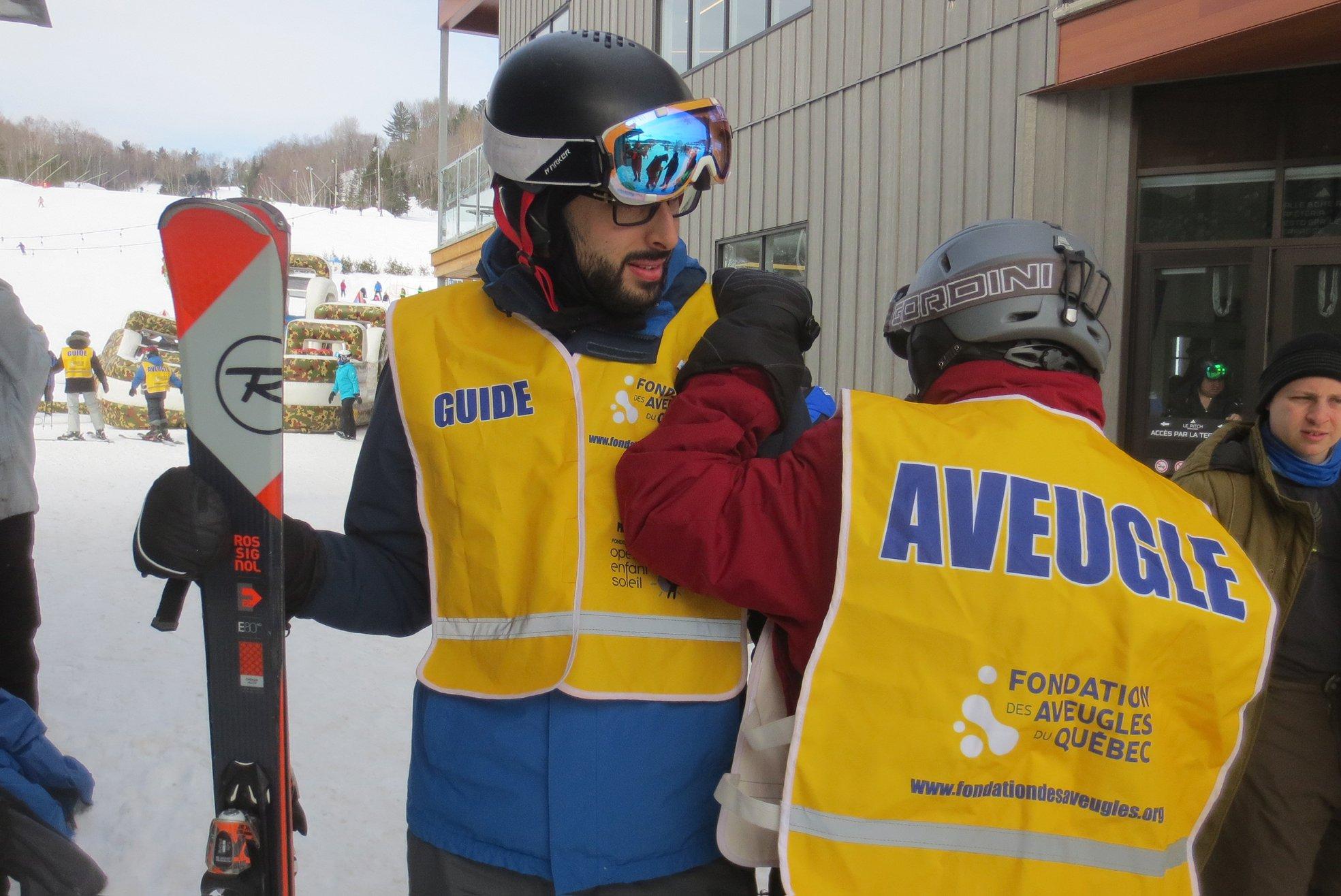 Une vue de dos d'un participant avec la main sur l'épaule d'un guide tenant des skis. – à Val Saint-Côme.