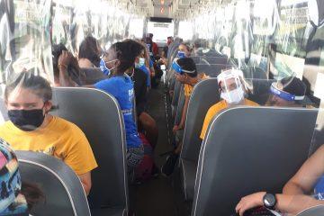 Une vue d'ensemble des participants et des moniteurs assis dans le bus portant différentes formes de masques et de visières.