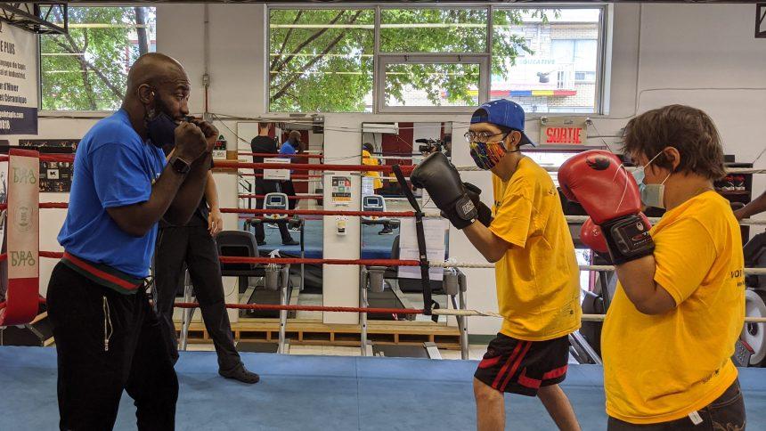 Ali Nestor sur le ring avec deux enfants de la Fondation des aveugles du Québec.