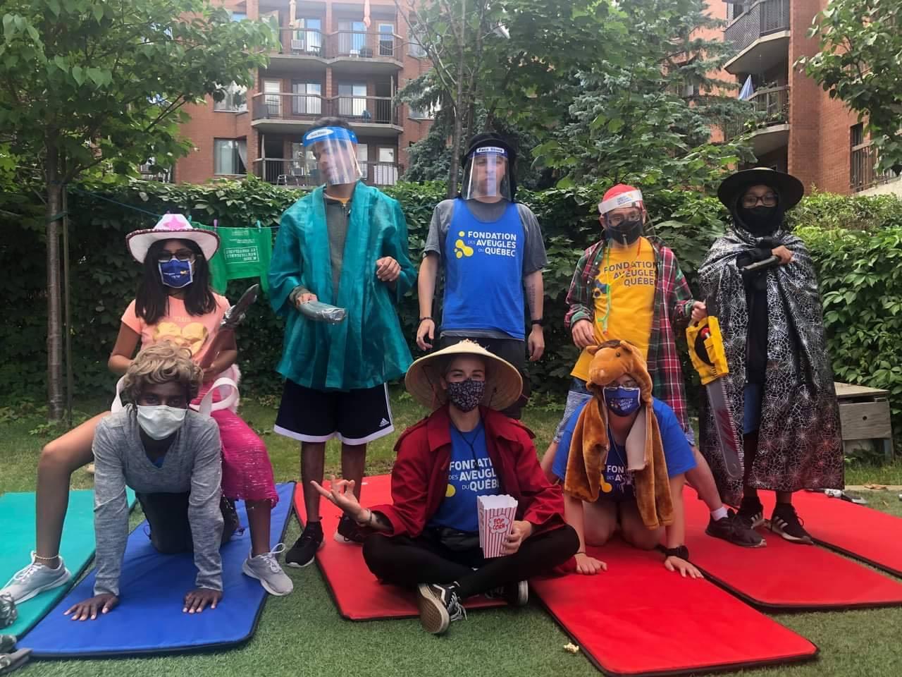 Quatre accompagnateurs et quatre participants posent pour la caméra dans des habits loufoques.