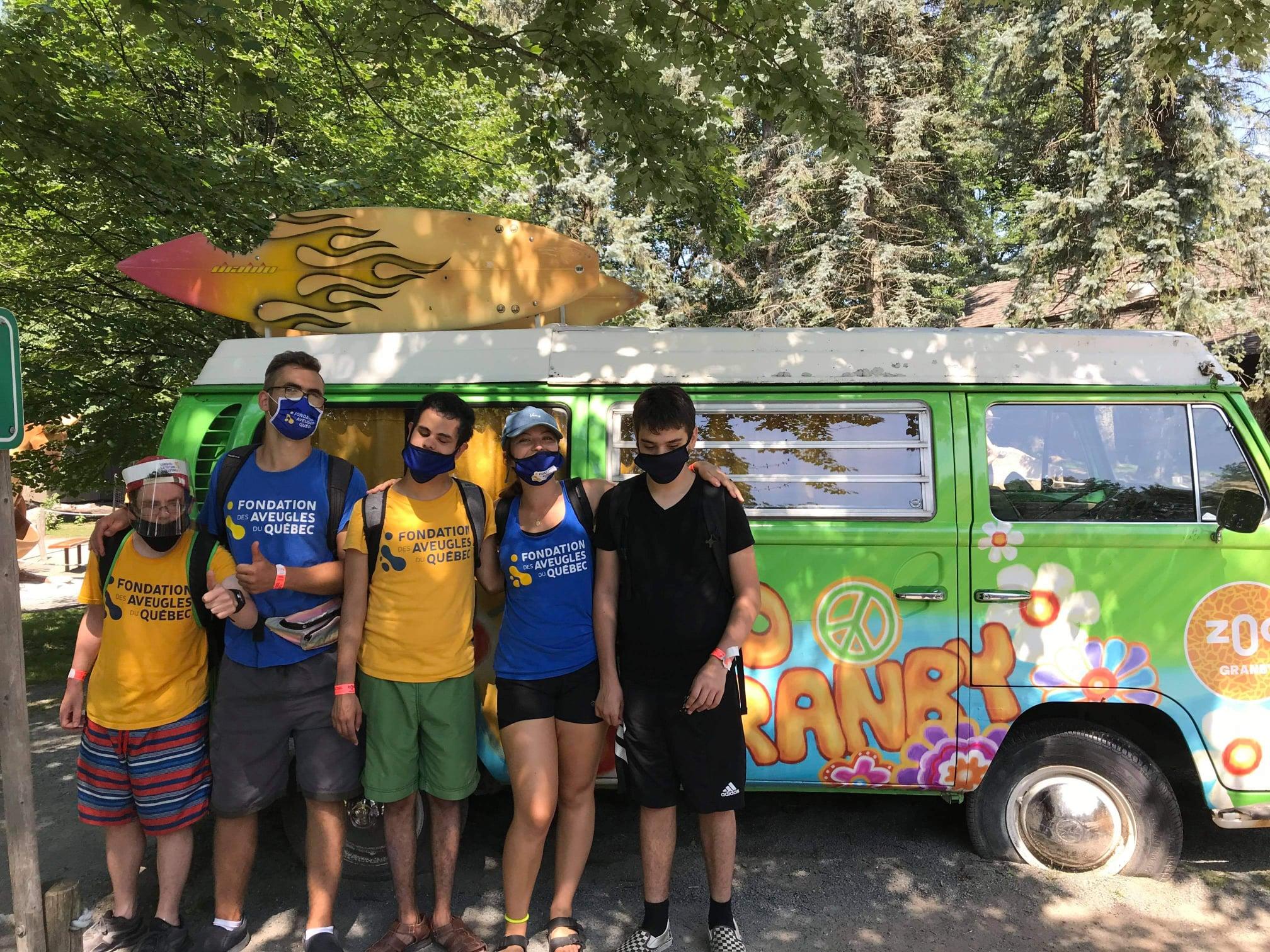 Deux accompagnateurs et trois participants posent pour la caméra devant une fourgonnette peinte avec des couleurs vintage.