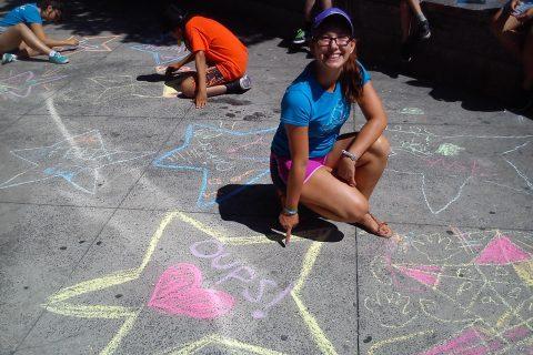 Jessica est accroupie devant un dessin sur l'asphalte, à la craie, d'une étoile avec un cœur et le texte « Oups! » au centre.