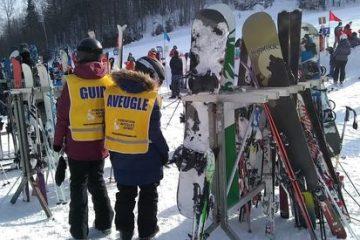 Un guide et un participant debout devant des équipements de ski