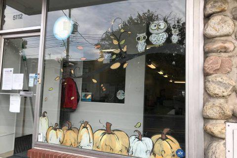 3 hiboux sont posés sur une branche à partir de l'extrémité droite de la fenêtre. Des citrouilles oranges et blanches sont alignées au bas de la vitre. Des feuilles jaunes, oranges et vertes sont éparpillées dans la fenêtre.