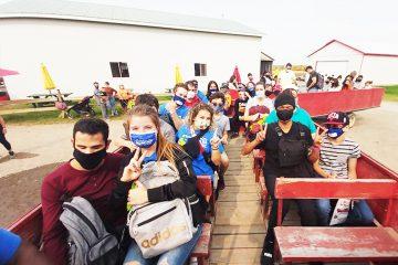 Moniteurs et participants en route vers la cueillette de pommes dans un chariot tiré par un tracteur.