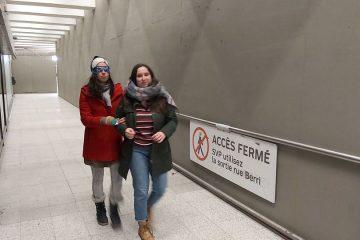 une femme accompagne une autre femme portant un bandeau sur les yeux dans le métro lors de la formation des monitrices et des moniteurs en 2019.