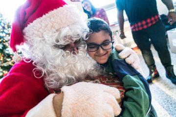 Un jeune participant donne un câlin au Père Noël lors du dépouillement de la FAQ en 2019.