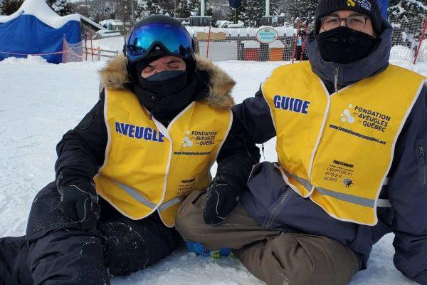 Un participant et un guide assis dans la neige regardent vers la caméra.