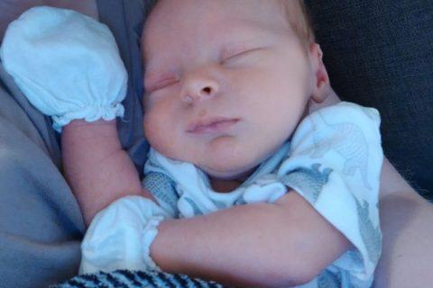 Un bébé naissant dort avec des gants protecteurs sur les mains.