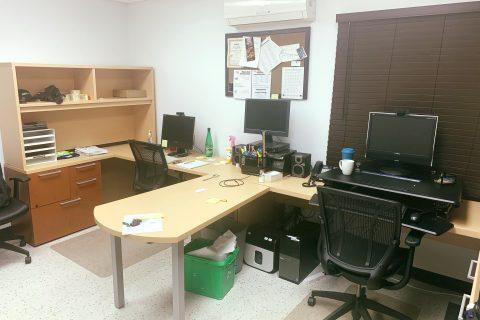 Une vue d'ensemble du bureau des loisirs de la rue Bennett. Une table de travail en forme de «T» sépare deux espaces de travail ayant chacun une chaise de travail et un ordinateur.