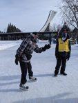 Un guide regarde en direction d'un participant en patin.