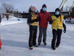 Deux accompagnatrices assistent un participant en patin.