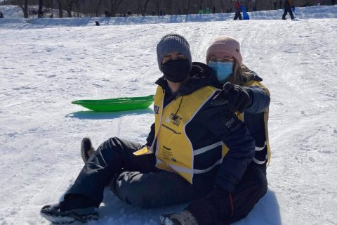 Une accompagnatrice pointant vers la caméra est assise avec un participant dans la neige.