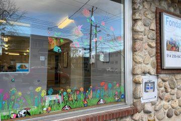 Au bas de la vitrine, des lapins sont dessinés parmi des branches d'herbes et des fleurs multicolores. Au centre de l'image, on y voit des oiseaux posés sur des branches d'arbres. Des mangeoires sont aussi accrochées aux branches.