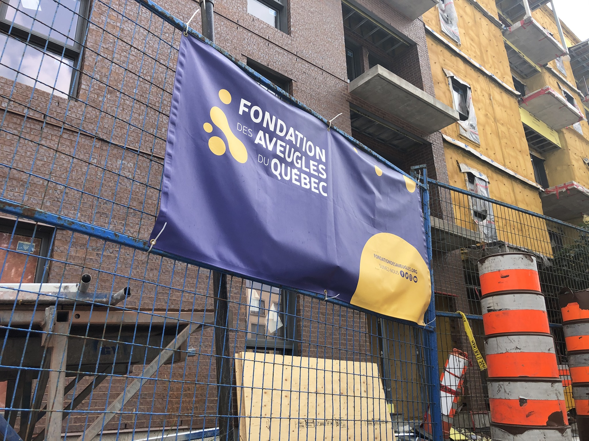Une bannière de la FAQ est posée sur une barrière de métal lors de la construction de l'immeuble au 9050 Sherbrooke Est.