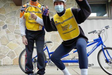 Un égo portrait d'une accompagnatrice avec les pouces levés et un participant. Un vélo-tandem est visible en arrière-plan.