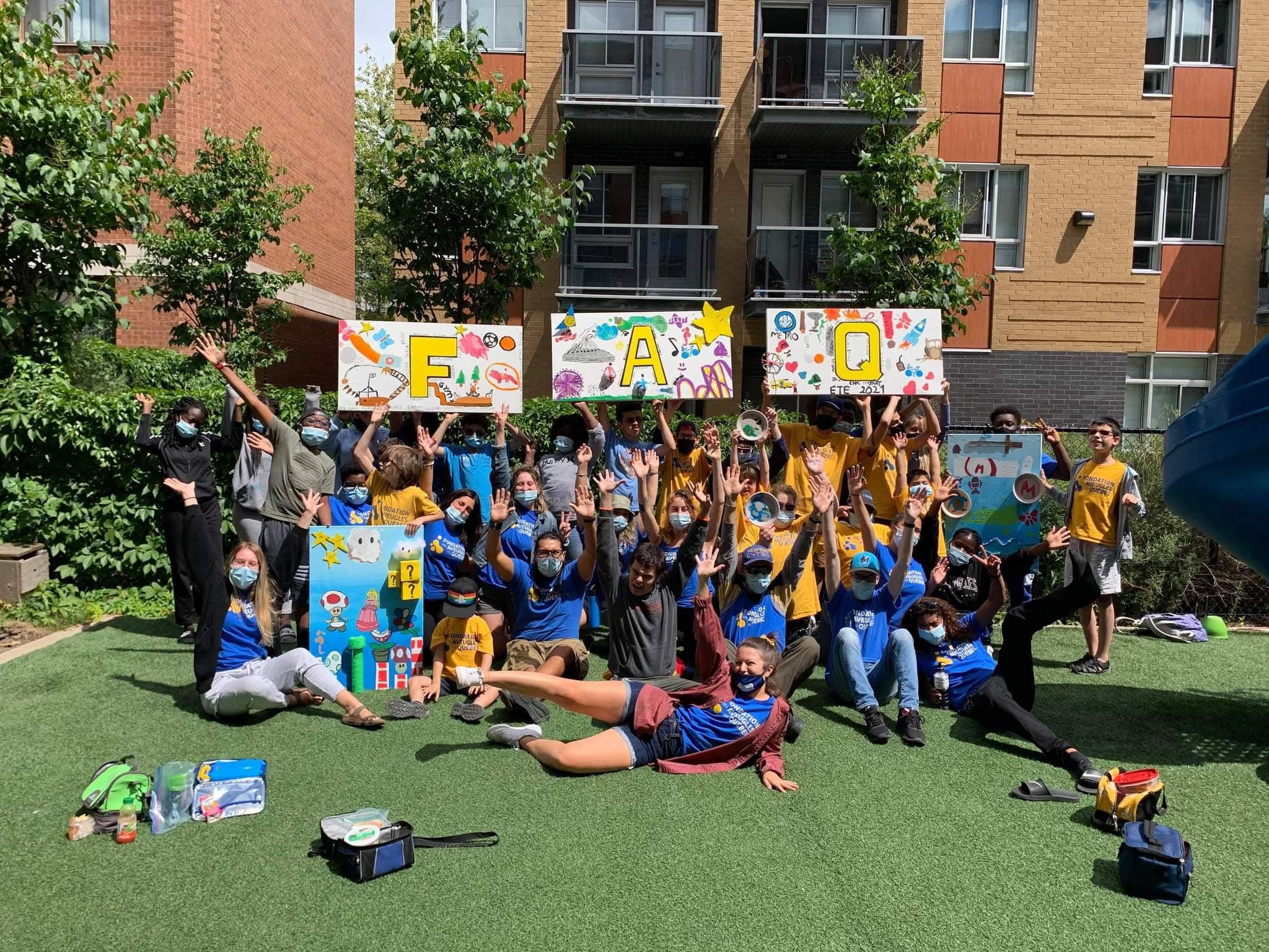 Description de l'image : Une photo de groupe avec la réalisation du projet artistique composé de 3 pancartes contenant les lettres «FAQ» décorés.